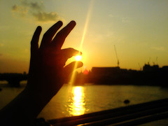 A hand against the sky appears to be holding the sun between thumb and forefinger