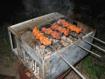 Kebabs roasting on an open barbecue made from a metal computer case