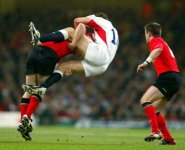 Welsh rugby player Shanklin tackling an opponent in mid-air.