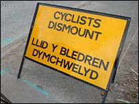 Road sign reads: Cyclists dismount, Llid y bledren dymchwelyd